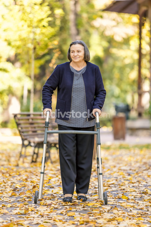 Woman with walker walking outdoors in autumn park