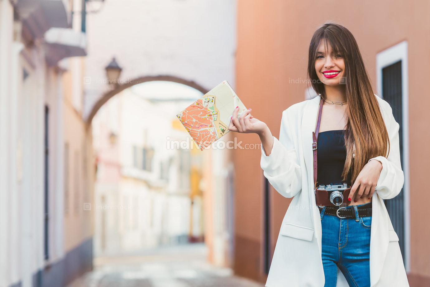 Young female traveler with camera and map on the street. Travel