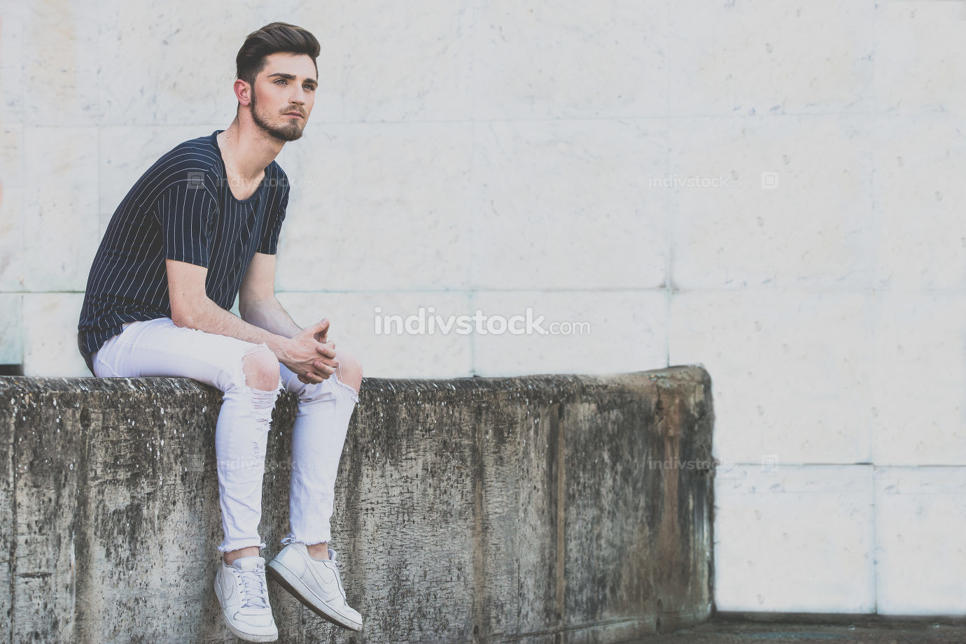 young man sitting on wall and thinking. Pensative guy