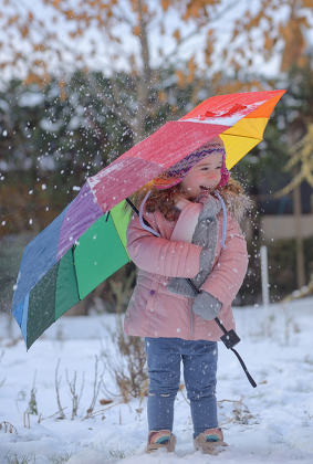 Little girl under umbrella in winter