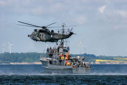 NATO rescue mission in sea with ship and helicopter.