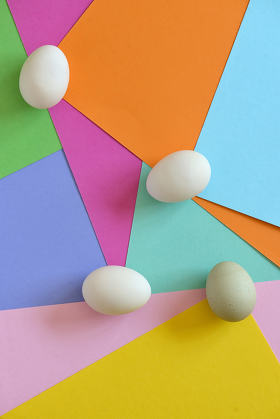 Unpainted eggs on color papers