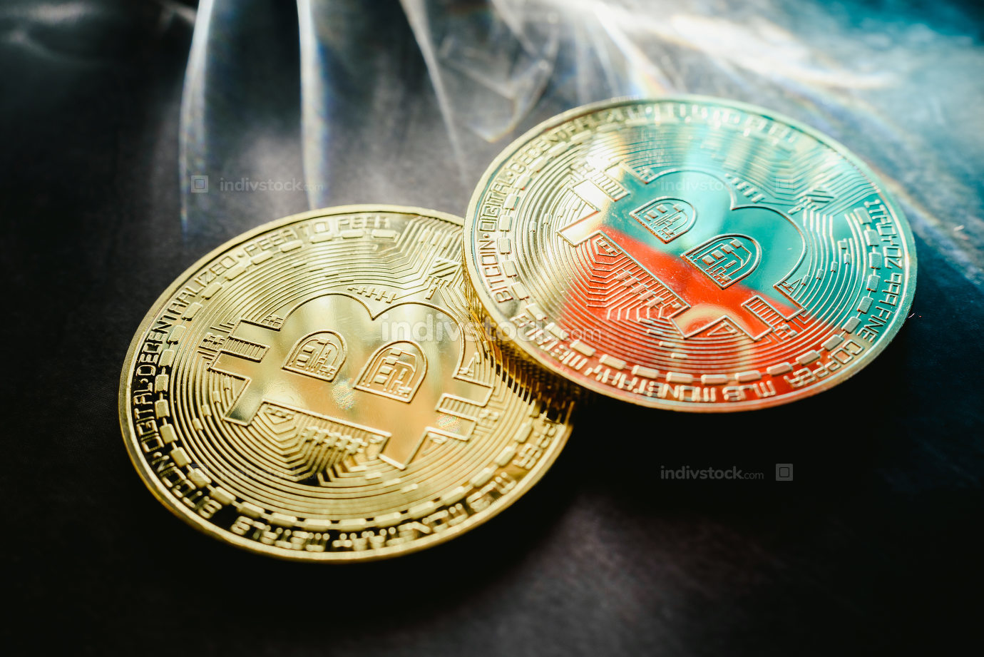 Bitcoin physical coins illuminated by light rays with dark backg