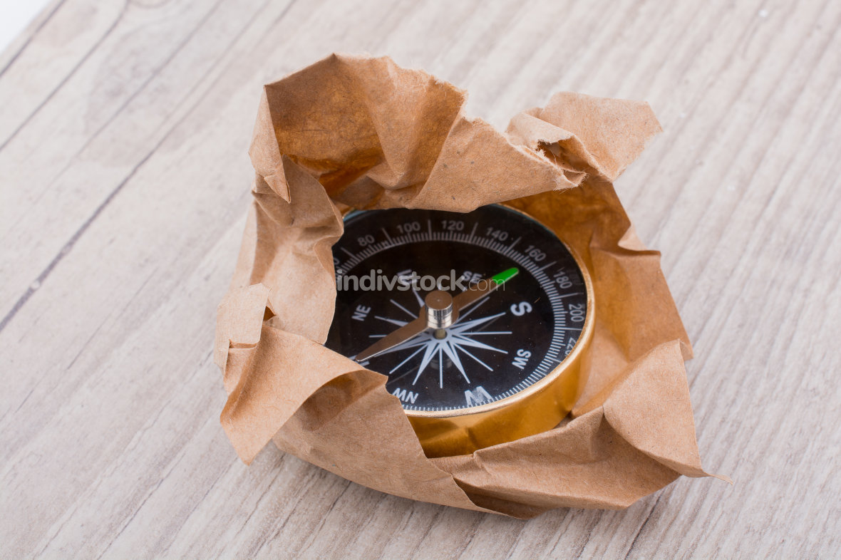Black compass  wrapped in brown paper