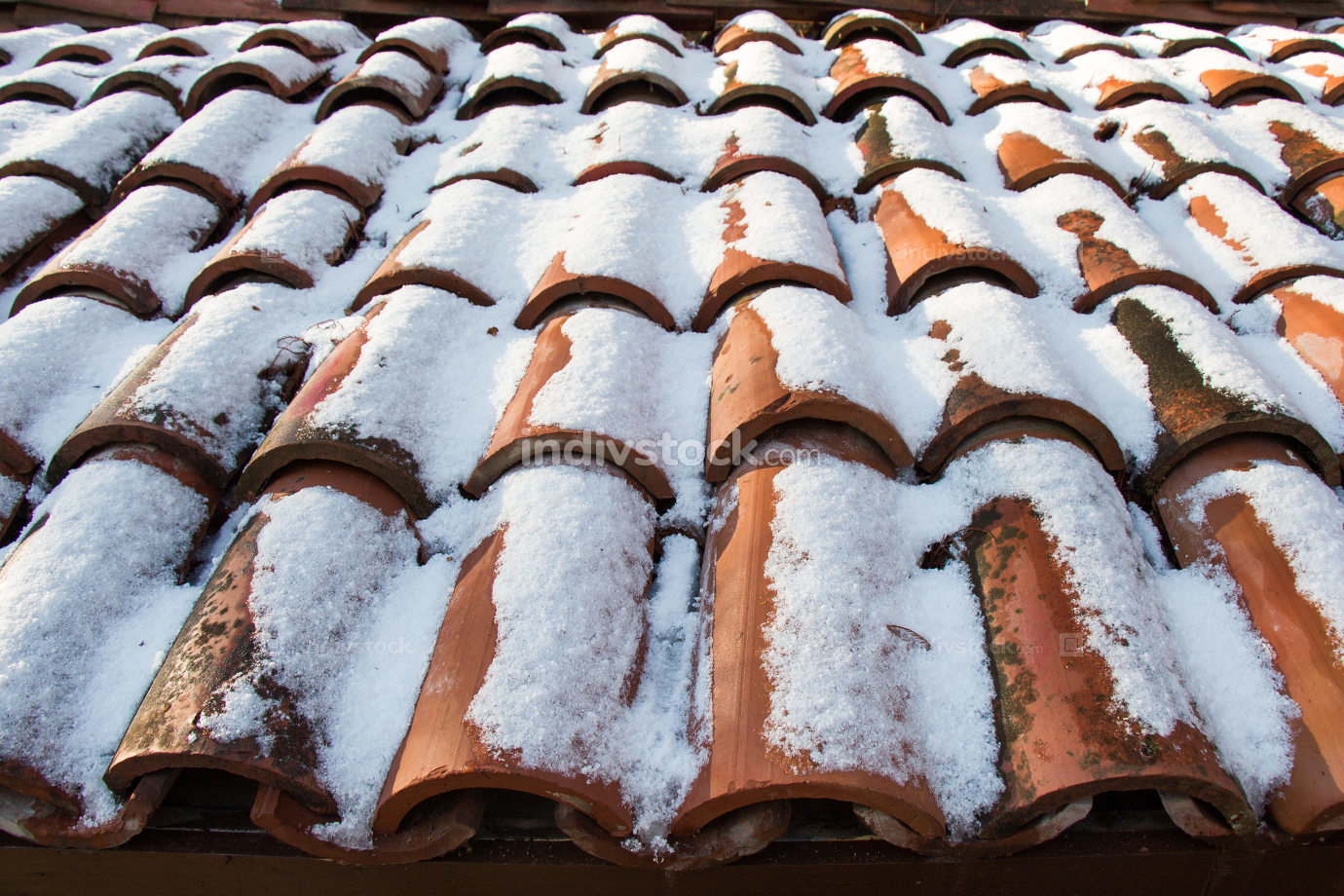 Brown tiles slightly covered with snow