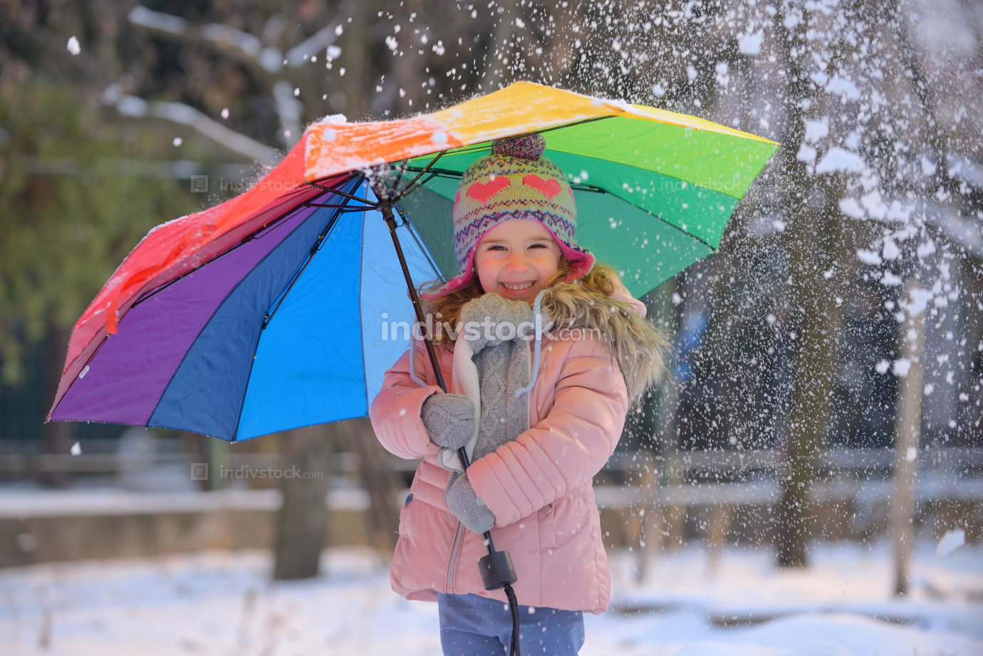 Little girl under umbrella in winter