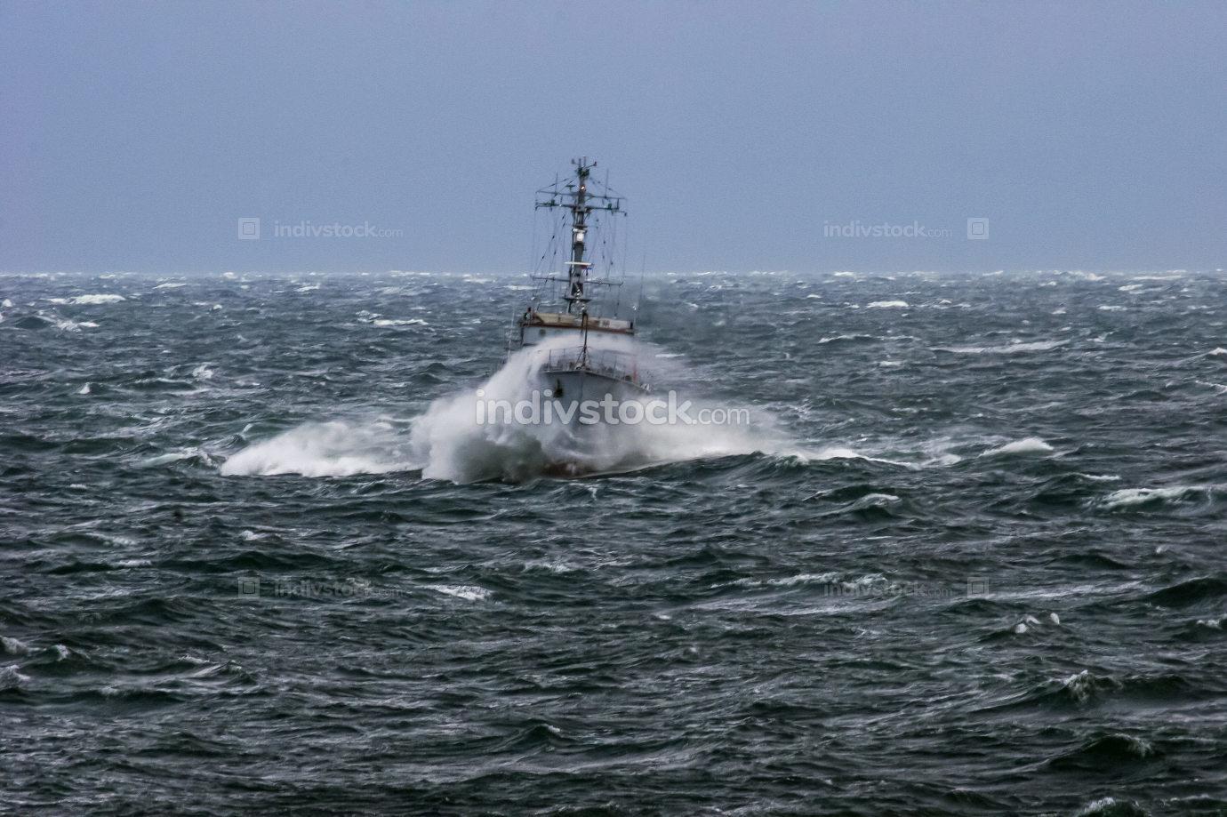 NATO military ship at sea during a storm.