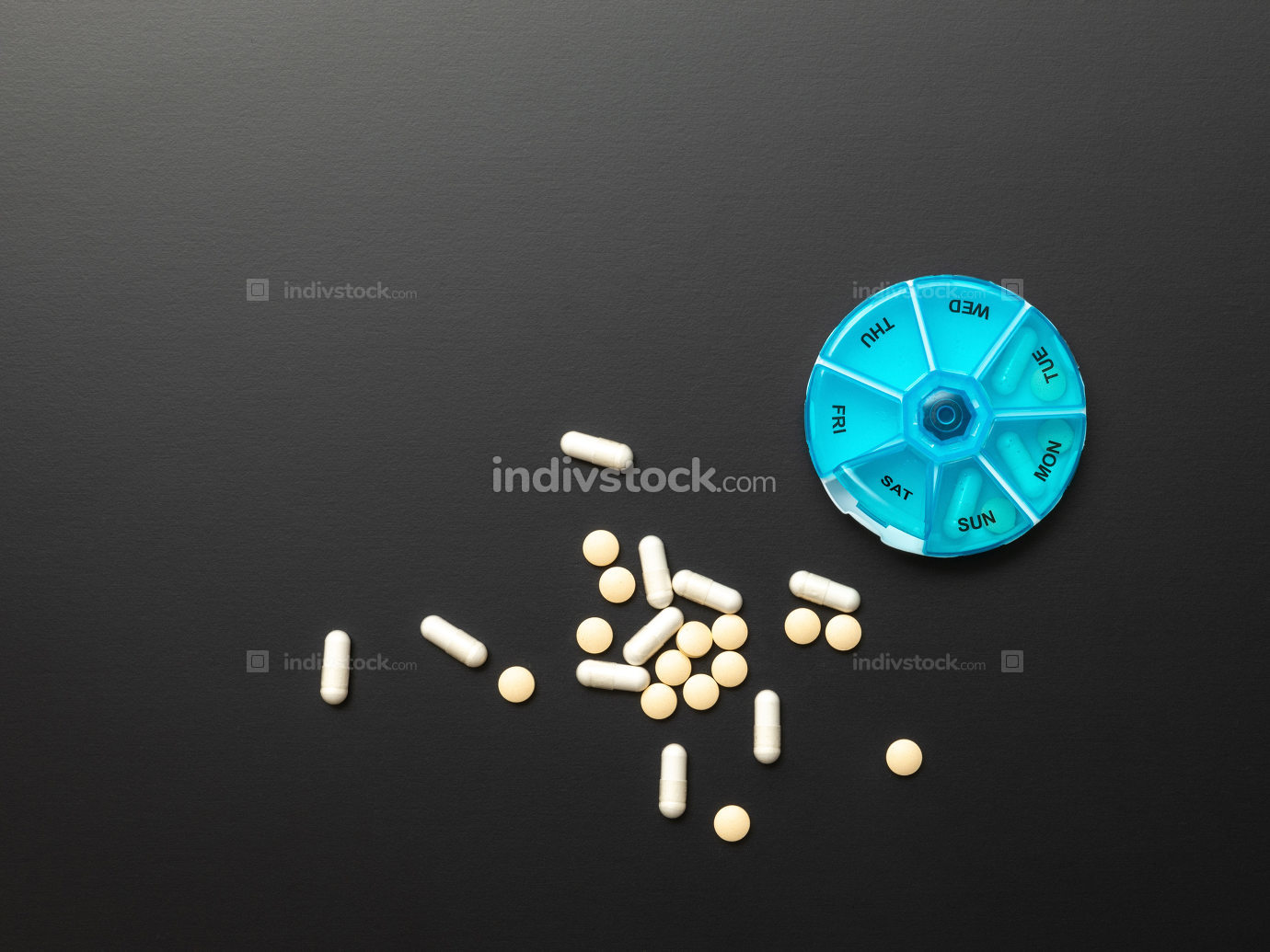 open pillbox with some pills