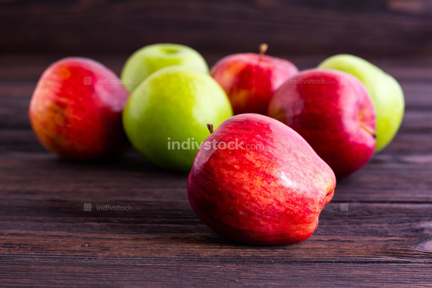 Red and Green Apples on wooden table.