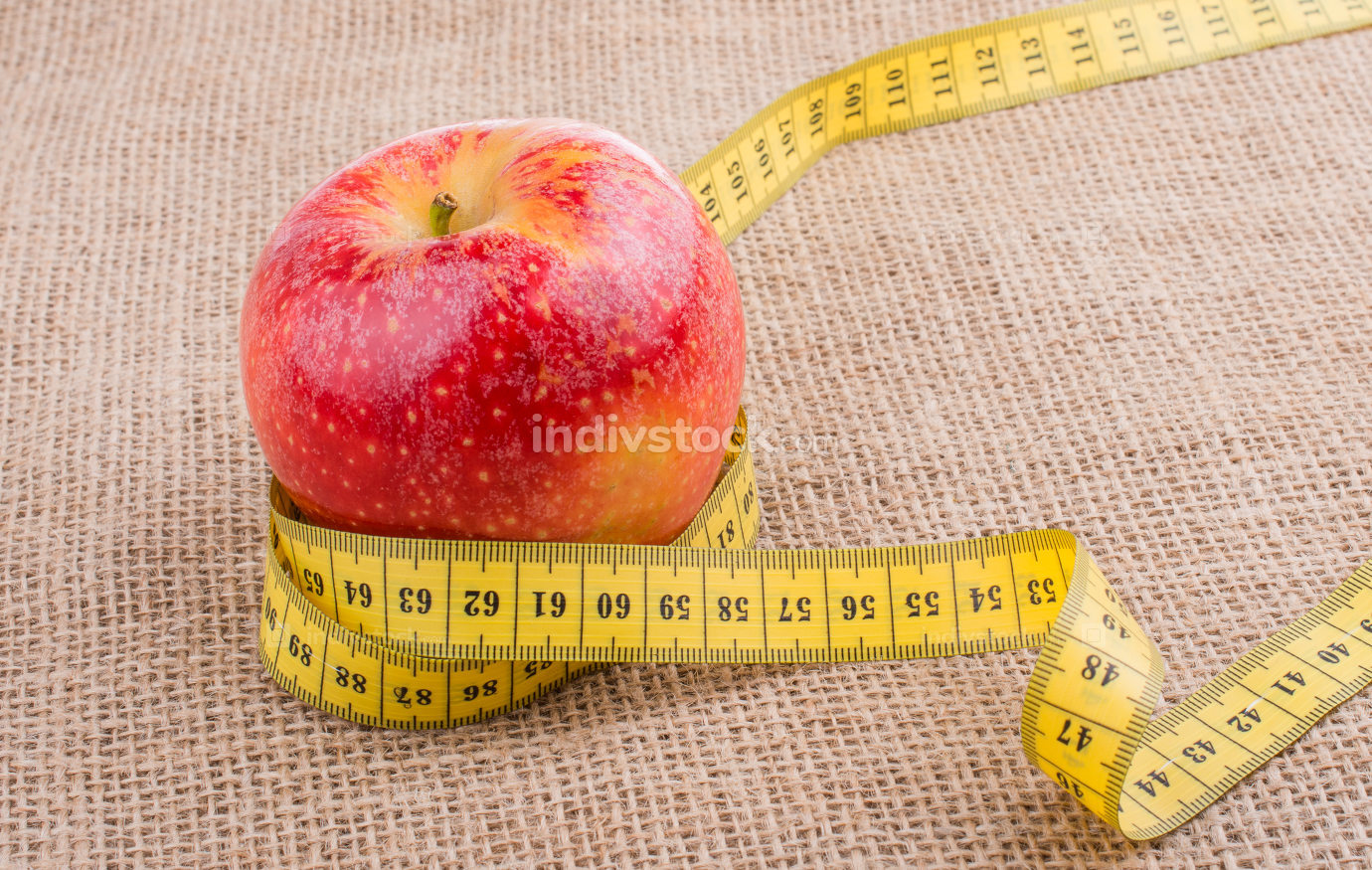Red apple with a measurement  tape on it