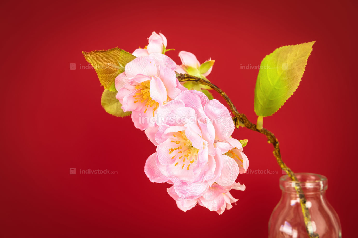 red background with artificial cherry blossoms