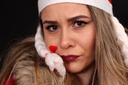 beautiful frown girl with santa hat in studio