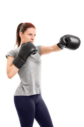 Beautiful young girl with boxing gloves punching