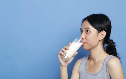 Beauty young mix-race asian women holding the milk glass ready to drink for health purpose in big bright blue colour background