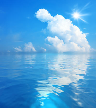 blue sky with white clouds and sun over the sea