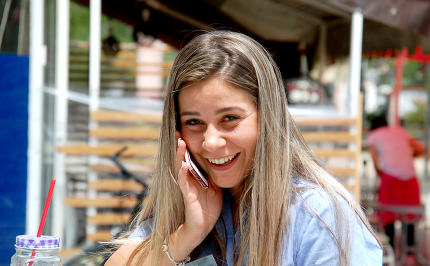 Cheerful young woman talking over smartphone.