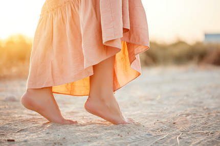 feet of a woman in a pink dress walking on the sand during sunse