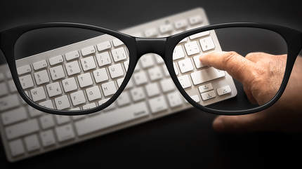 glasses with keyboard sharp and blurred