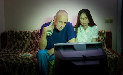 Middle-aged man and woman, watch television, looking sad, sittin