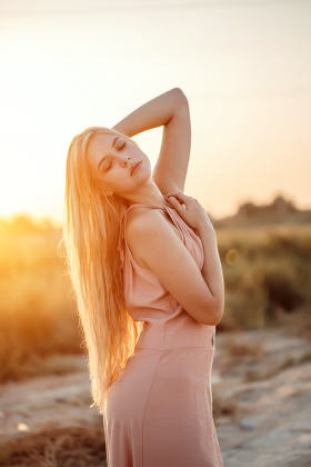 portrait of a young beautiful Caucasian blonde woman in a pink d