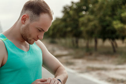 portrait of Caucasian guy in azure t-shirt looking at fitness tr