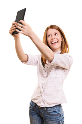 Smiling young girl taking a selfie with her tablet