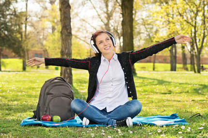 Student in a park with arms outstretched as if she