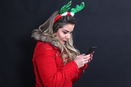 studio portrait of a girl with headband using smartphone,