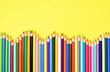 Wave of coloring pencils on yellow background