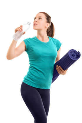 Young girl holding an exercise mat and drinking water