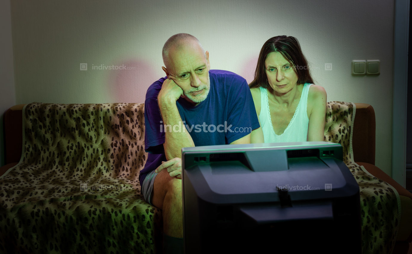 A couple of adult lovers, sitting on a couch watch movie on tele