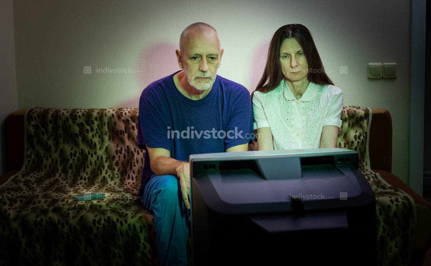 Adult man and woman, watch television, looking sad, sitting on a