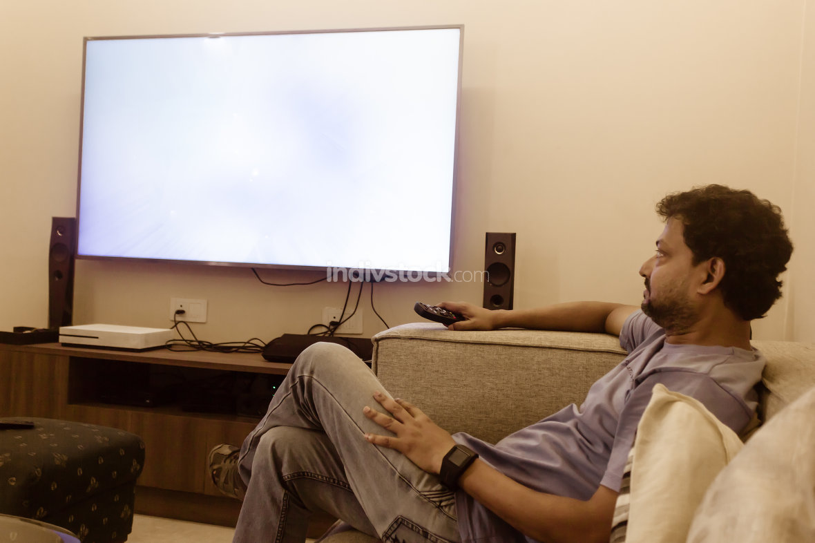 Asian man 40-44 watching tv at home in living room