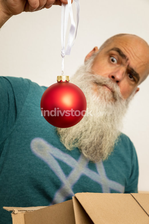 bearded man looking at red christmas ball