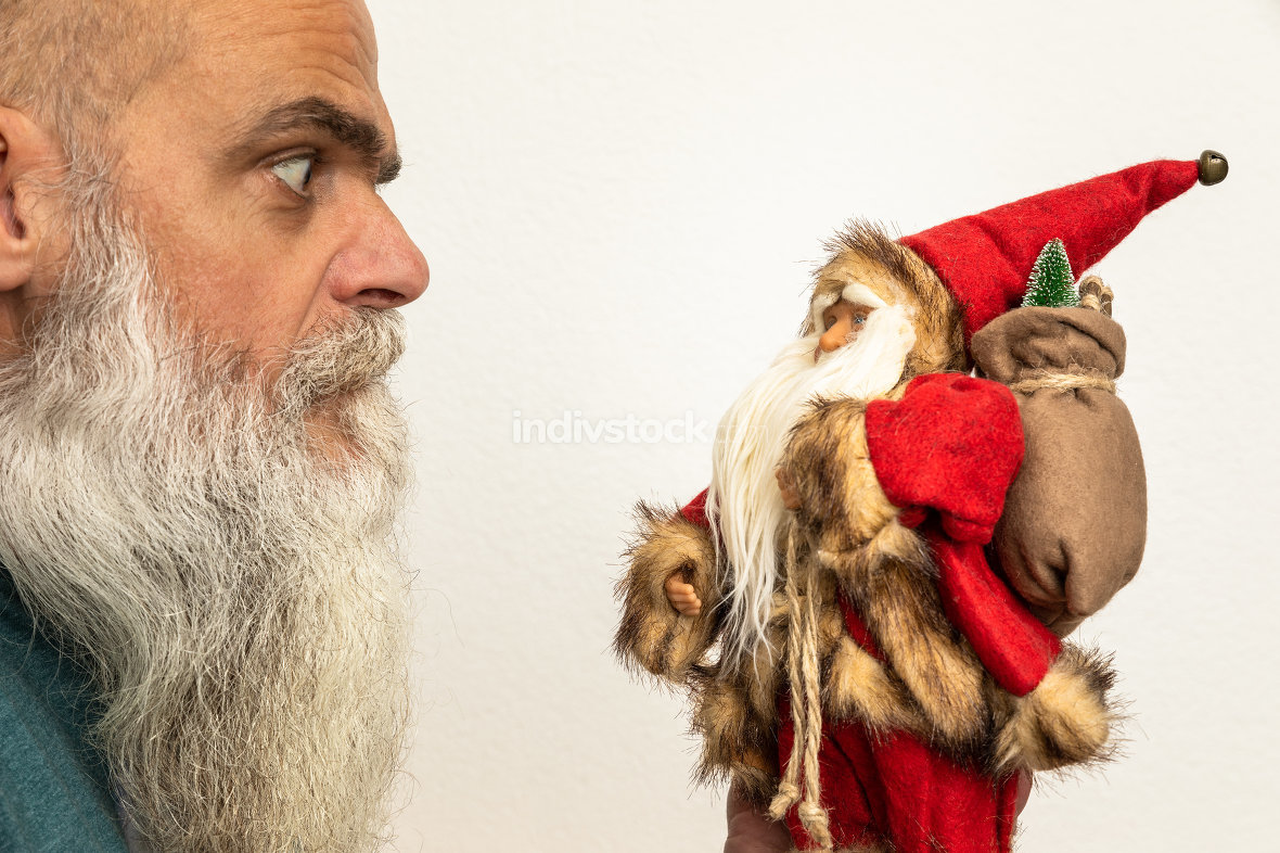 bearded man looking to a Santa Claus puppet