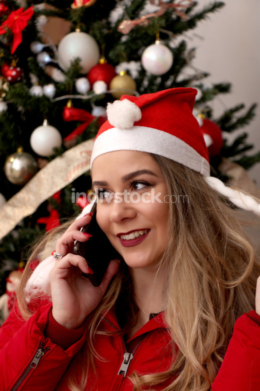 beautiful girl with santa hat using smartphone
