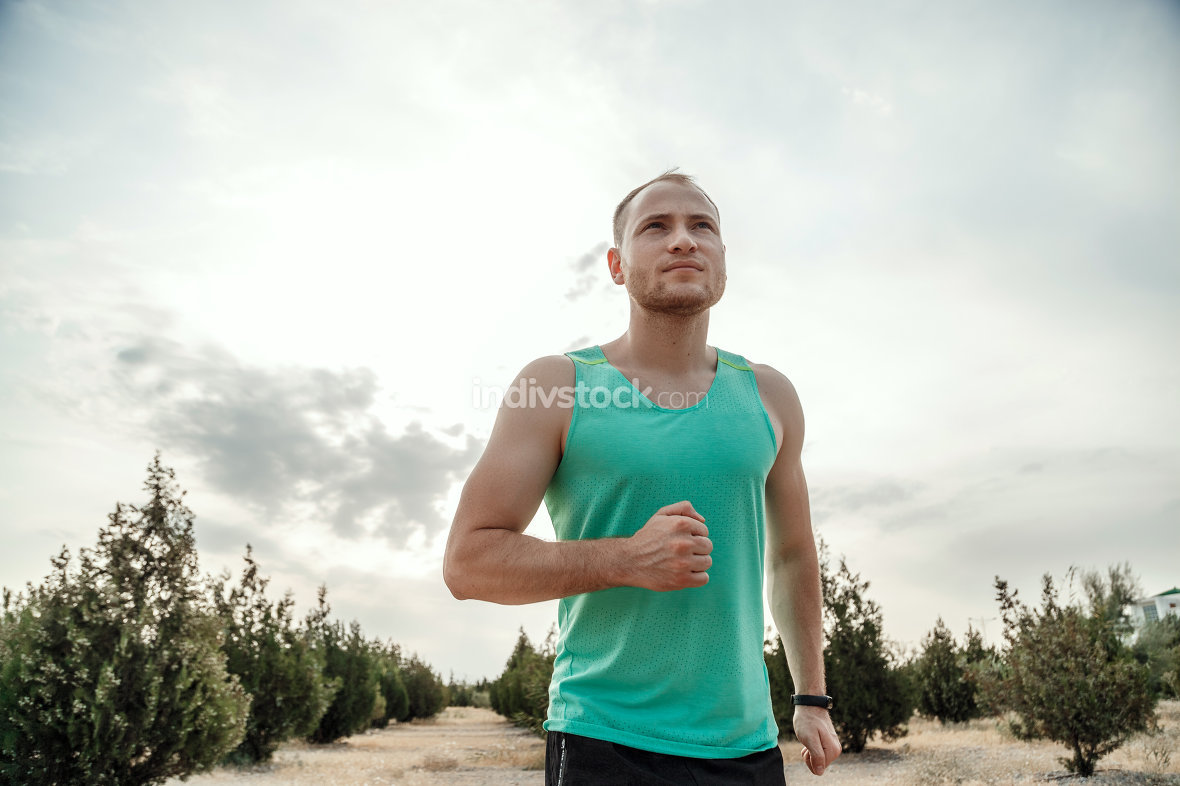 Caucasian guy in a blue t-shirt and black shorts,running over ro