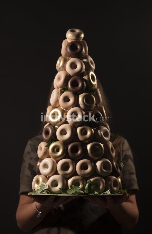 girl holding glazed donuts , studio shot, black background