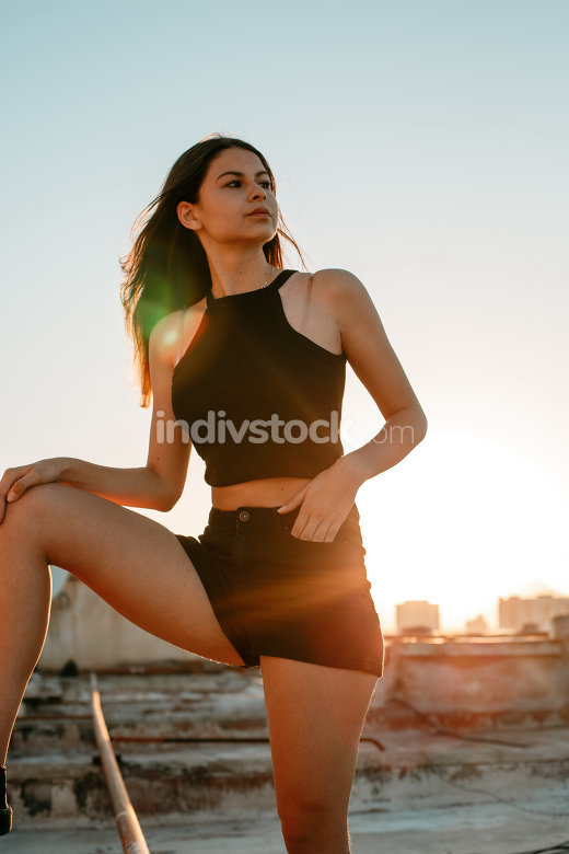 portrait of a young brunette girl in black sneakers,black shorts