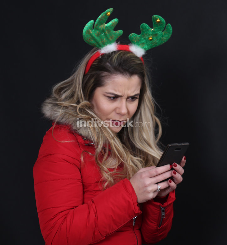 studio portrait of a girl with headband using smartphone,