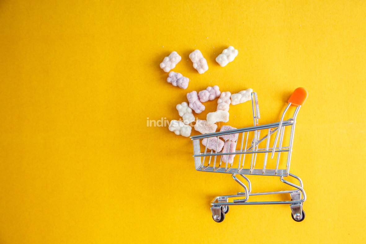 vitamins in the form of bears on a yellow background with a toy