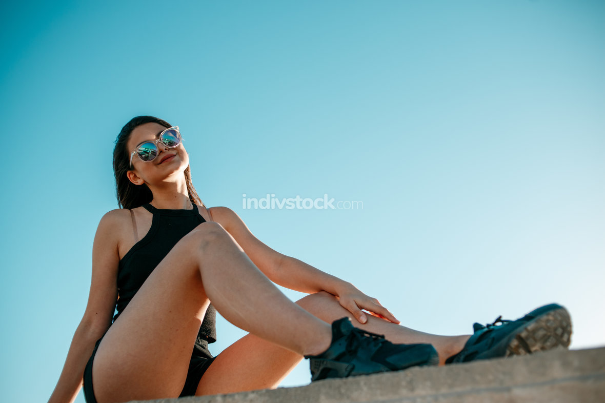 young brunette girl in black sneakers,black shorts and a black s