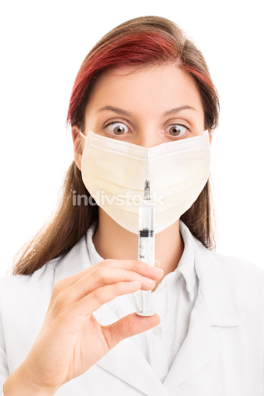 Young doctor wearing surgical mask and holding a syringe