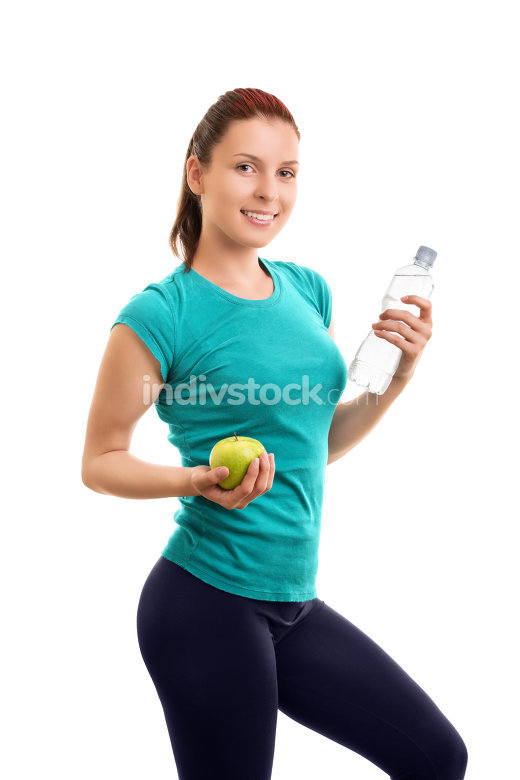 Young girl holding an apple and a bottle