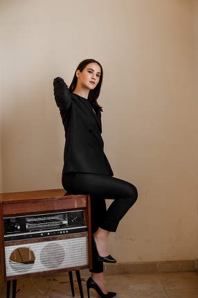 a beautiful Caucasian young woman in a black pantsuit and black sandals stands next to a vintage record player