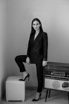 a beautiful Caucasian young woman in a black pantsuit and black sandals stands next to a vintage record player. black and white photo