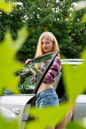 a blonde woman between an open car door