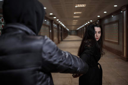 a young beautiful woman tries to escape from a robber in black clothes . in the underpass. at night