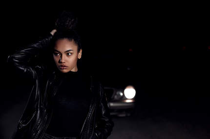 a young girl, African American mulatto girl in a leather jacket and black clothes poses