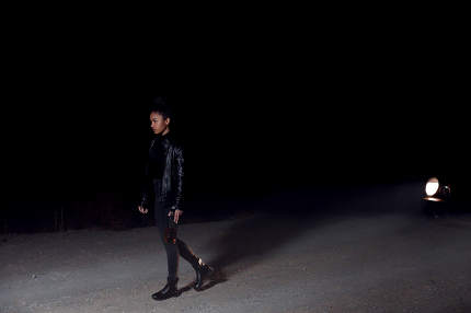 a young girl, African-American mulatto girl in a leather jacket and black clothes is walking